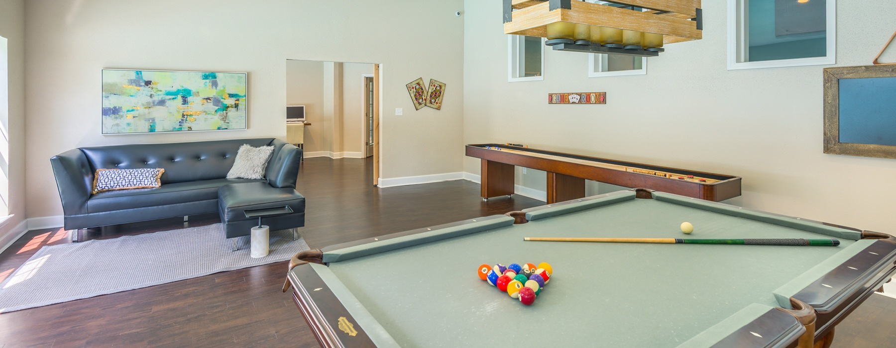 spacious, game room with large windows and overhead lighting